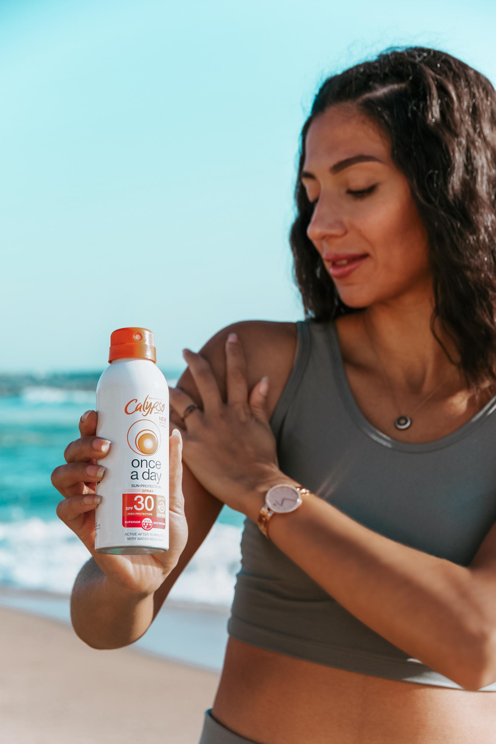 Girl on a beach applying Calypso Once a day spray spf30